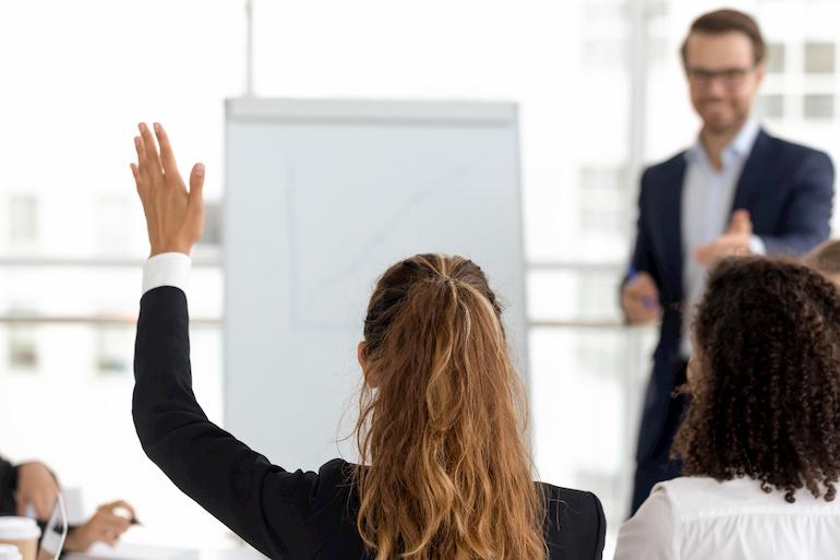 Eine Frau hebt initiativ ihre Hand.