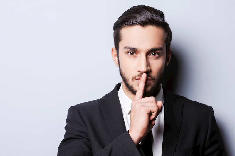 Mann hält Finger als Sperrvermerk vor seine Lippen.