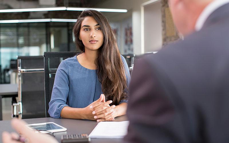 Eine Frau sitzt beim Vorstellungsgespräch einem Mann gegenüber