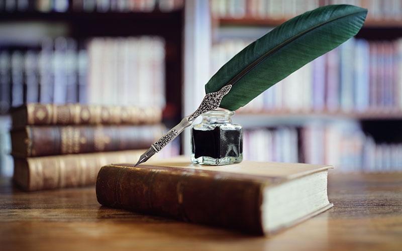 Eine edle Schreibfeder und ein Tintenfass platziert auf einem alten Buch