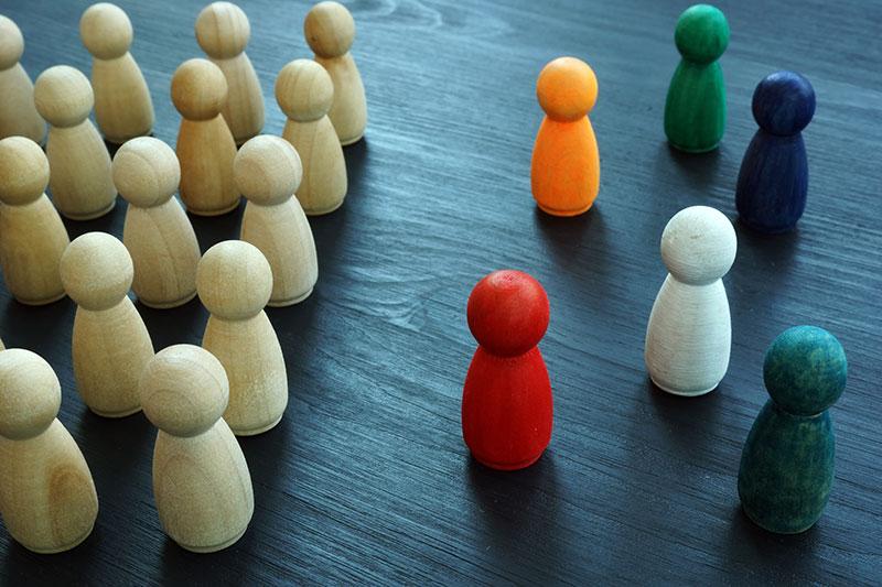 Viele gleiche, einfarbige Figuren stehen geordnet einzelnen bunten Figuren gegenüber