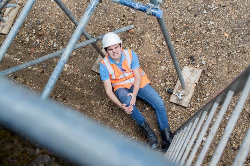 Ein Bauarbeiter liegt auf dem Boden und hält sein rechtes Knie