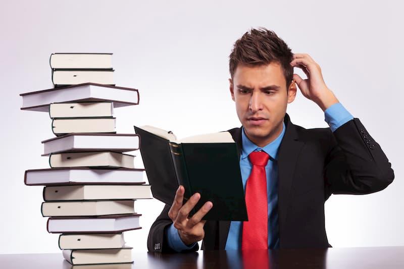 Mann schaut in ein Buch und ist verwirrt.