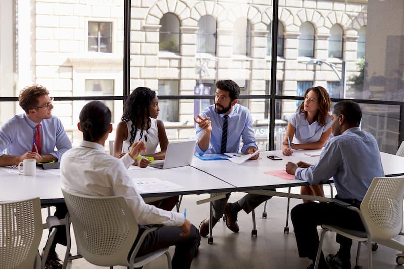 Mehrere Menschen am Tisch bei einer Teambesprechung