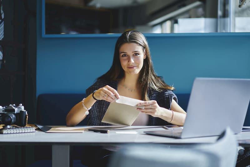 Eine Frau lächelt und öffnet einen Briefumschlag