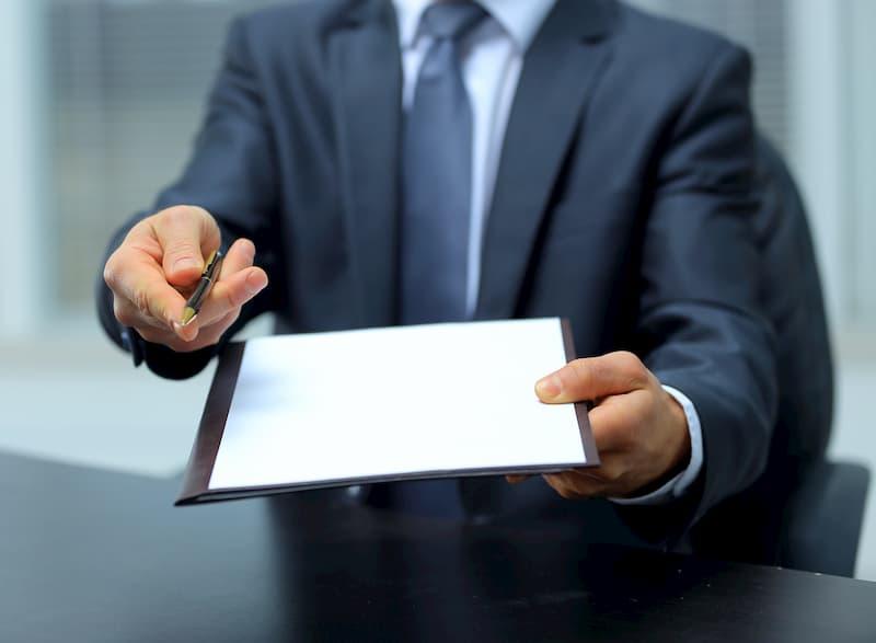 Ein Mann hält Stift und Papier entgegen