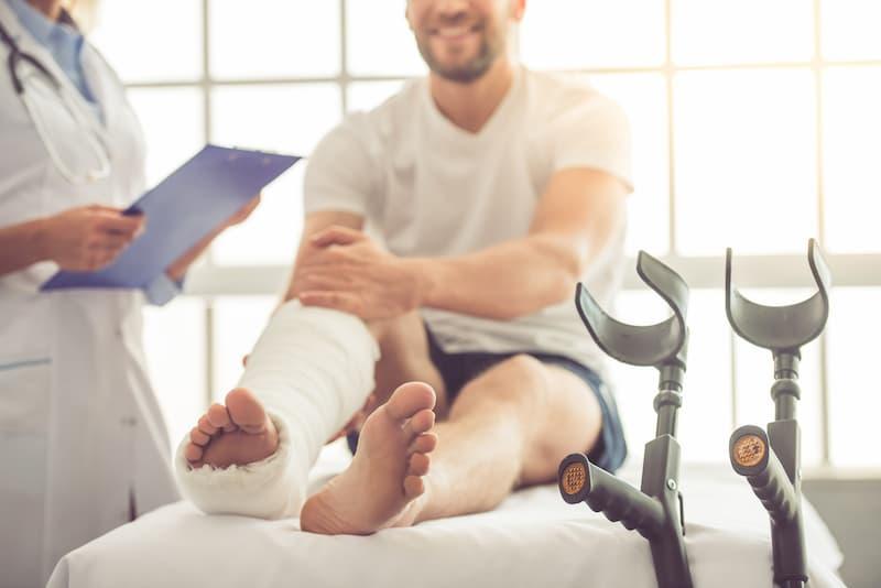 Ein Mann mit verbundenem Bein und eine Ärztin