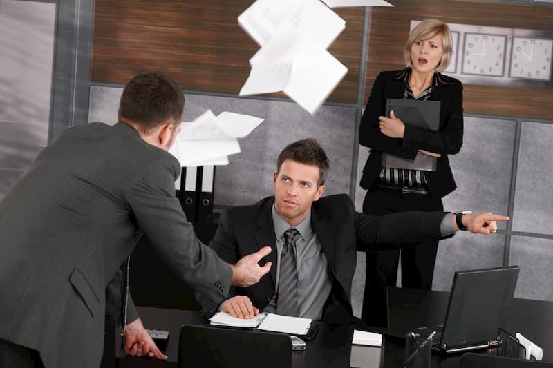 Ein Mann schaut wütend auf einen weiteren Mann und eine Frau im Hintergrund