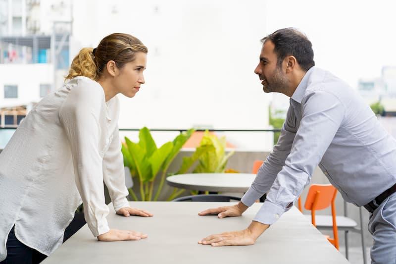 Ein Mann und eine Frau lehnen auf dem Tisch und starren sich an