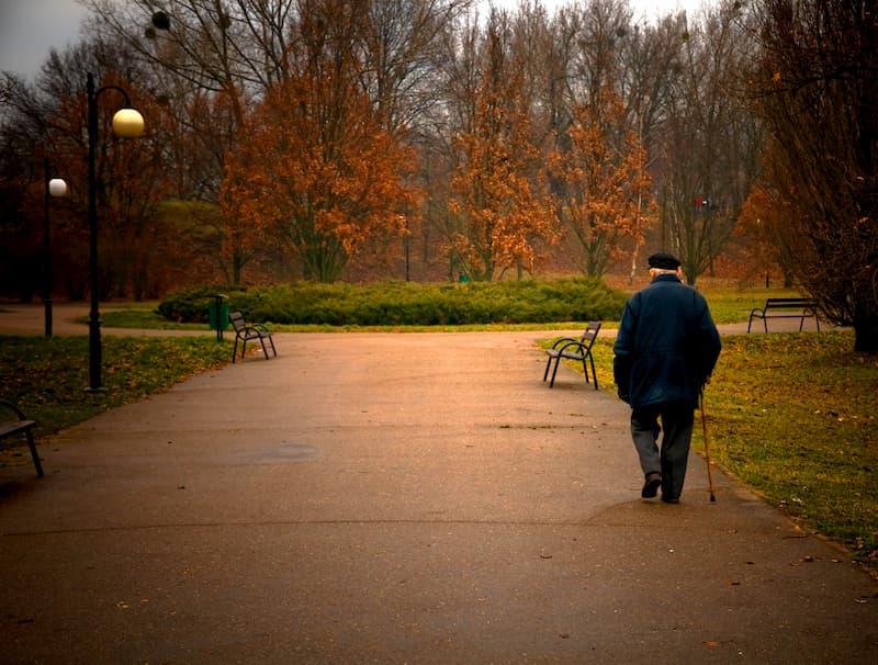 Armer alter Mann mit Krückstock geht durch den Park