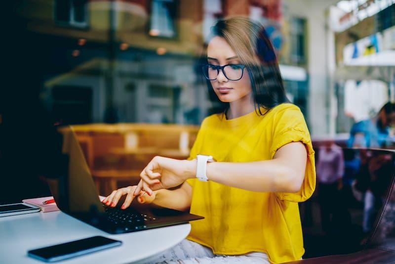 Eine Frau schaut auf die Uhr bei der Arbeit um keine Minusstunden zu machen