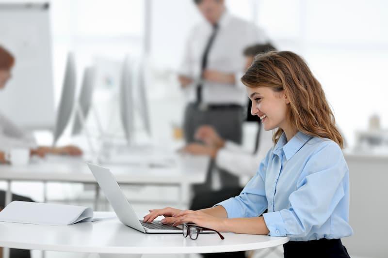 Eine Frau sitzt nur mit Laptop an einem Tisch in einem Büro mit Clean-Desk-Policy