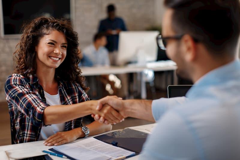 Eine junge Frau schüttelt die Hand vom Chef, nachdem sie den Ausbildungsvertrag unterzeichnet hat