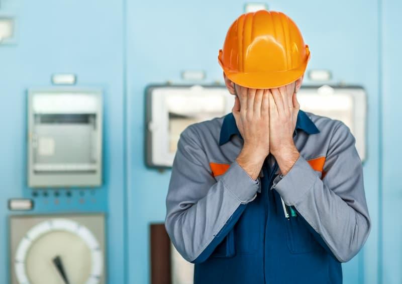 Ein Mann in Arbeitskleidung schlägt die Hände vors Gesicht aufgrund einer verhaltensbedingten Kündigung