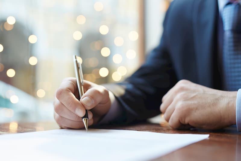 Ein Mann unterschreibt seinen Arbeitsvertrag