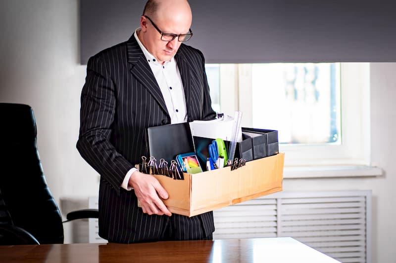 Ein Mann hat seine Materialien in einem Karton gepackt, denn er hat eine personenbedingte Kündigung erhalten