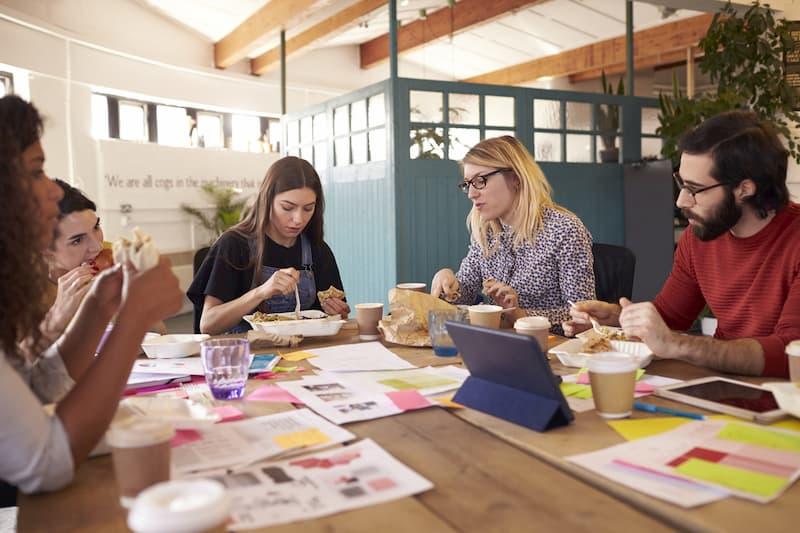 Mitarbeiter essen zusammen beim Frühstück - ein typisches Benefit Zu den typischen Mitarbeiter-Benefits gehört ein gemeinsames Essen