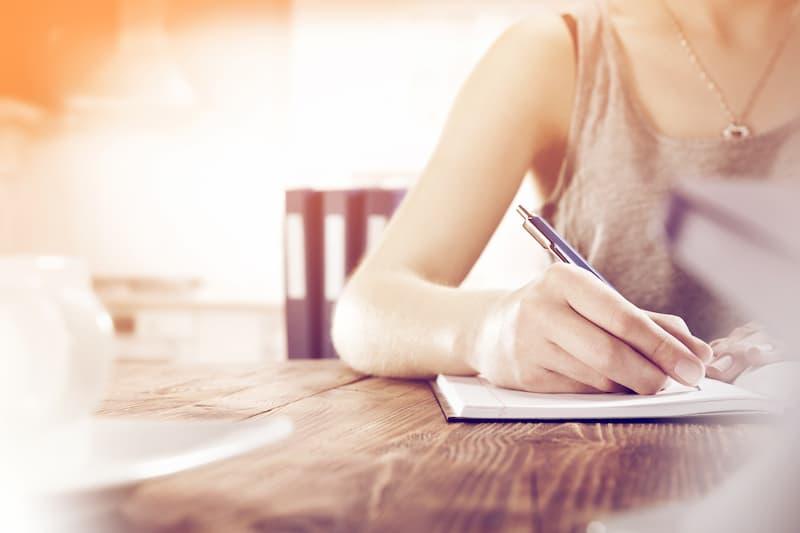 Eine Frau schreibt eine Kündigung, dabei muss sie manche Kriterien einhalten