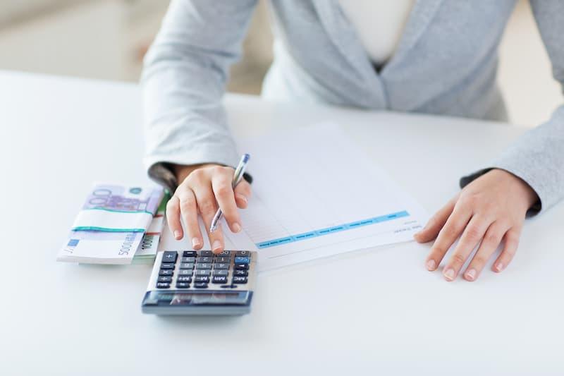 Eine Frau sitzt vor Euro-Scheinen und einem Taschenrechner und berechnet die Karenzentschädigung