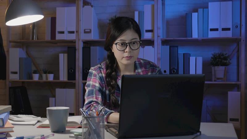 Eine Ghostwriterin sitzt am Laptop und schreibt die Bewerbung für jemand anderes