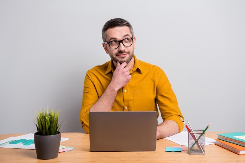 Ein Mann sitzt nachdenklich vor einem Laptop und nutzt einen Gehaltsrechner
