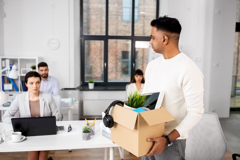 Ein Mann ist im Büro und hat nach der Kündigung einen Karton mit privaten Sachen in der Hand