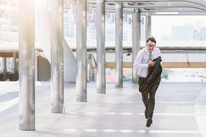 Ein Mann rennt auf dem Parkplatz, denn er ist zu spät - ab wann ist es Arbeitszeitbetrug?