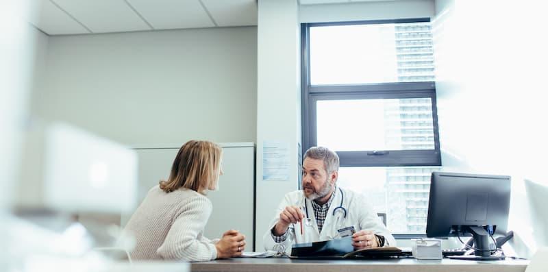 Eine Frau holt sich eine Arbeitsunfähigkeitsbescheinigung vom Arzt