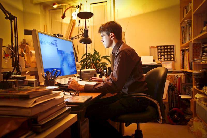 Ein Mann sitzt im Home-Office am PC und arbeitet aufgrund der Vertrauensarbeitszeit in der Nacht