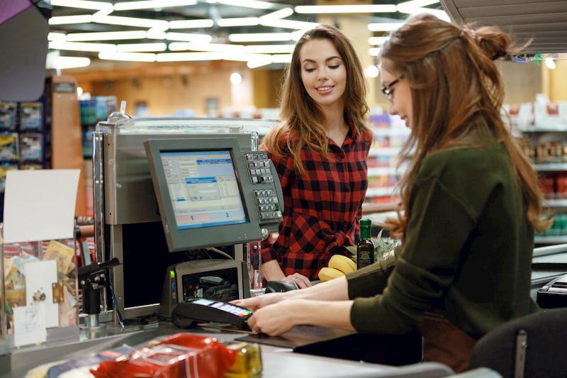 Eine Schülerin arbeitet in ihrem Minijob an der Kasse eines Supermarktes und bekommt Mindestlohn