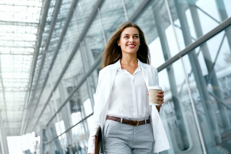 Eine Frau kehrt bei der Wiedereingliederung in den Job zurück und geht am Büro entlang