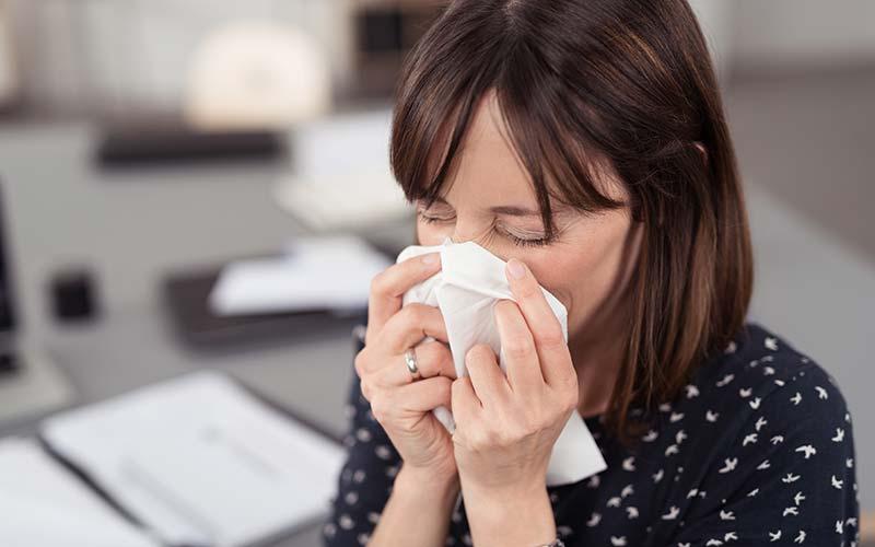 Eine kranke Frau niest auf der Arbeit in ein Taschentusch