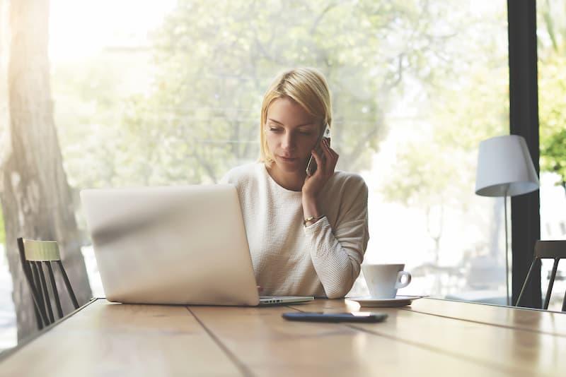 Eine Frau sitzt im Homeoffice am Laptop und telefoniert