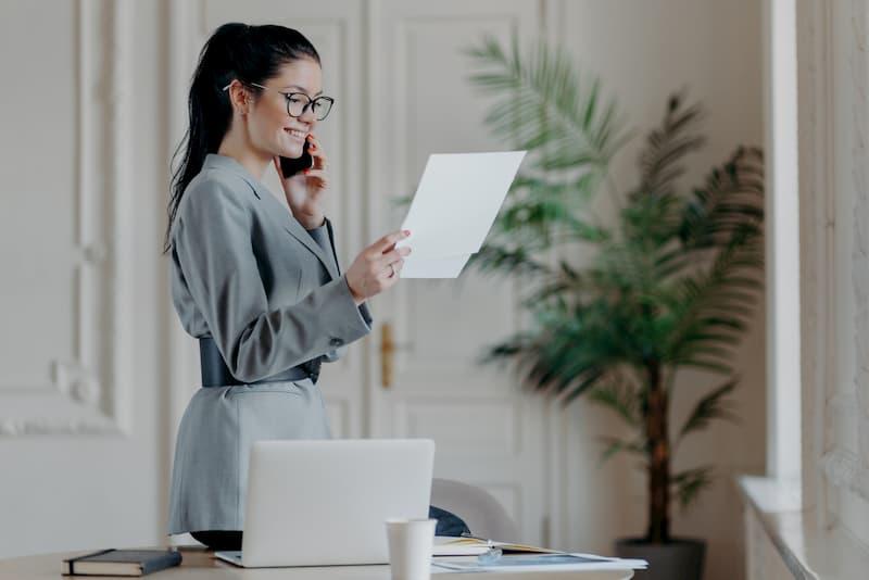 Eine junge Frau ist in ihrer Wohnung und hält ihr Ausbildungszeugnis in der Hand