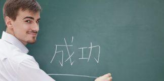 Ein Mann schreibt die chinesische Sprache auf eine Tafel. ein Beispiel für Hard Skills