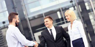 Eine Frau steht neben zwei Männern, welche die Hände schütteln, das Wettbewerbsverbot lässt den Mann nur bei diesem Unternehmen arbeiten