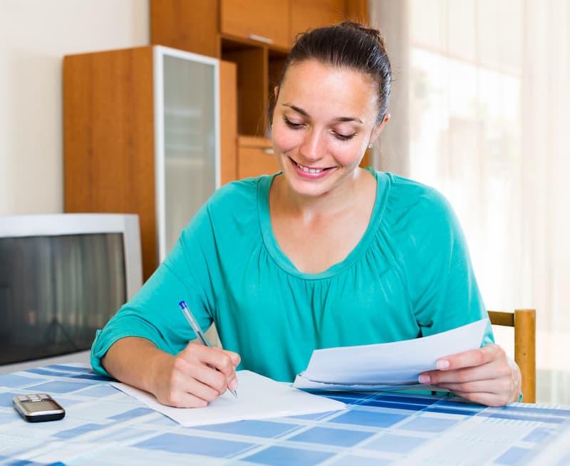 Eine Frau sitzt am Tisch und trägt eine Bonuszahlung in die Steuererklärung ein