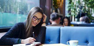 Eine junge Frau schreibt an ihrem Berichtsheft
