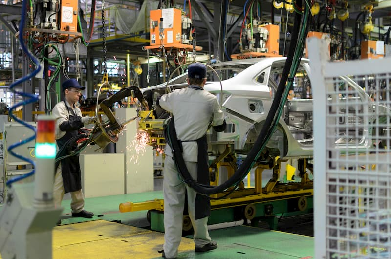 Männer als Zeitarbeiter in einer Autofabrik