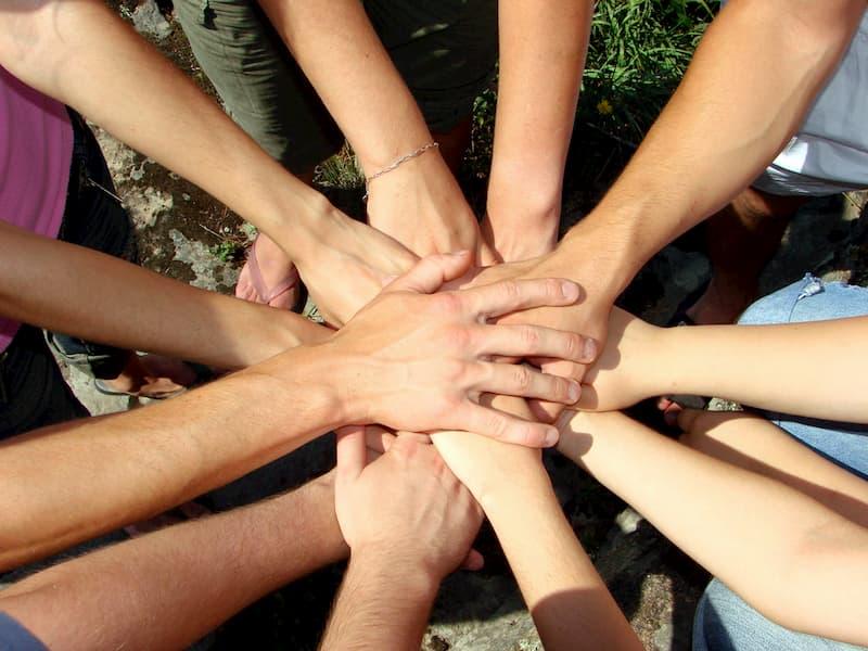 Aufeinander gelegte Hände sind ein Symbol für Teamwork