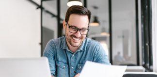 Ein junger Mann freut sich und betrachtet ein Dokument, in diesem steht sein Einstiegsgehalt