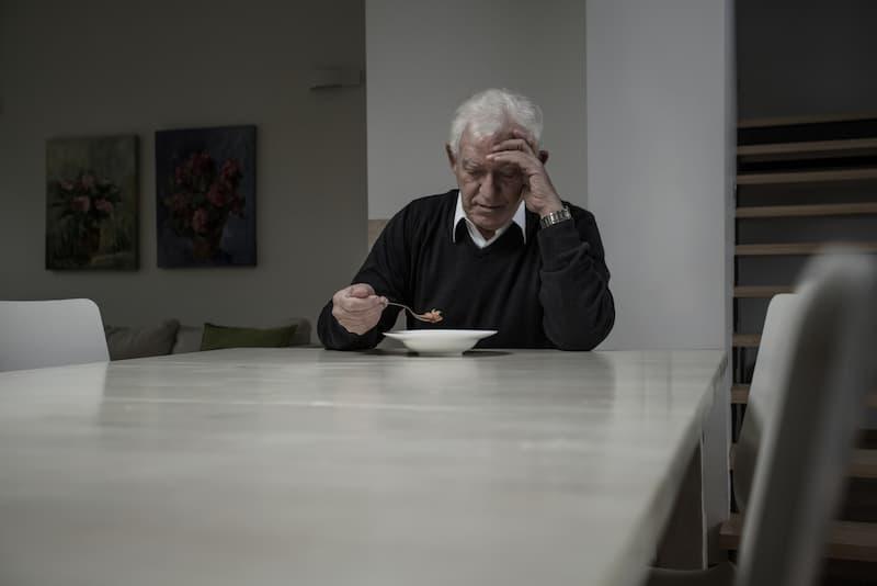 Ein Mann leidet am Empty-Desk-Syndrom und sitzt alleine Zuhause am Tisch und ist traurig