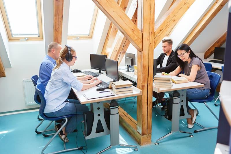 Mitarbeiter sitzen an einem Arbeitsplatz, der im Sinne des Desk-Sharing gestaltet ist