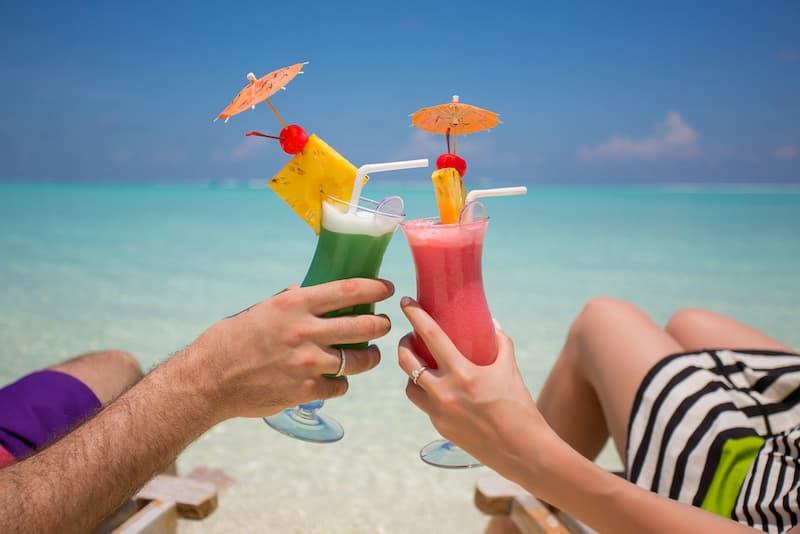Zwei Menschen haben Erholungsurlaub und trinken Cocktails am Strand