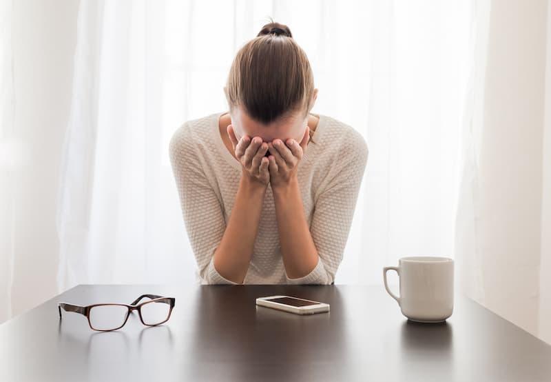 Eine Frau sitzt am Tisch und ist traurig, denn sie leidet unter der Doppelbelastung durch Familie und Beruf
