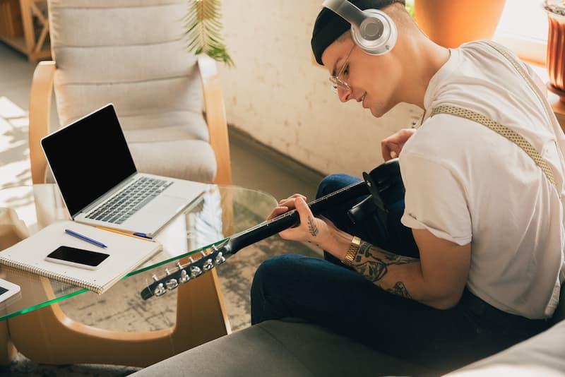 Ein Mann hat Rufbereitschaft, währenddessen kann er Zuhause Gitarre spielen