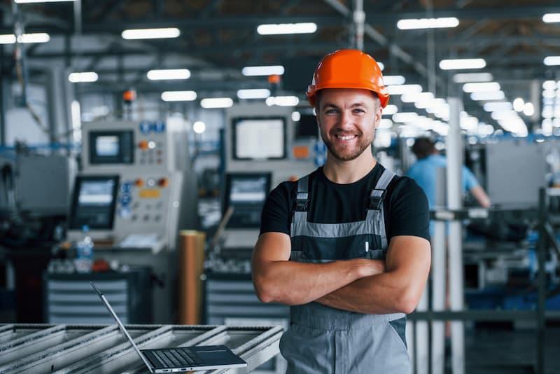Ein glücklicher Mann in der Werkshalle mit einer hohen Mitarbeiterzufriedenheit