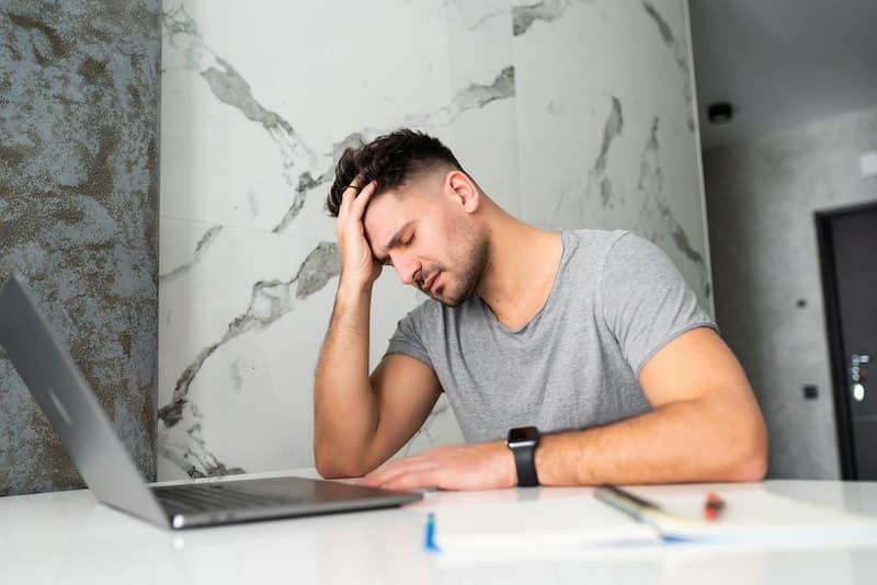 Ein Mann sitzt besorgt vor dem Laptop nach seiner Freistellung