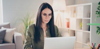 Eine Frau sitzt vor dem Laptop, sie ist auf Jobsuche.