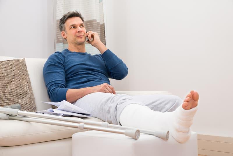 Ein Mann mit gebrochenem Bein telefoniert, er erhält Krankengeld